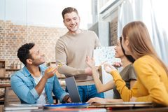 Smiling young man showing his work to fellow students and feeling curious. Cheerful students. Positive emotional young people feeling happy while sitting at the Royalty Free Stock Photo