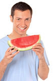 Smiling young man showing a slice of watermelon. Isolated on white background royalty free stock photography