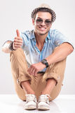Smiling young man showing the thumbs up gesture Stock Photography