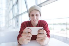 Smiling young man sits in a cafe and uses a smearphone. Attractive man watches a video on a smartphone royalty free stock photography