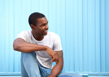 Smiling young man sitting against blue wall looking away Stock Photo