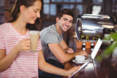 Smiling young man sitting at bar and using laptop Royalty Free Stock Photos