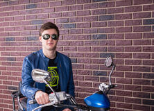Smiling young man sitting on a blue motorbike Royalty Free Stock Images