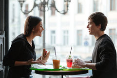 Smiling young man sitting in cafe with sister drinking juice Royalty Free Stock Image