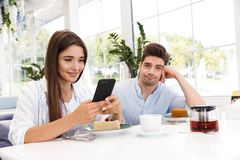 Smiling young man sitting at the cafe table. Smiling young men sitting at the cafe table while his girlfriend using mobile phone stock image