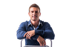 Smiling young man sitting on chair backwards Stock Photos