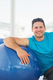 Smiling young man sitting with fitness ball at gym Royalty Free Stock Photo