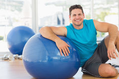 Smiling young man sitting with fitness ball at gym Royalty Free Stock Images