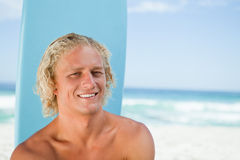 Smiling young man sitting in front of the ocean with his surfboa Royalty Free Stock Image