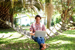 Smiling young man sitting in hammock with laptop Royalty Free Stock Image