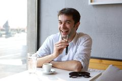 Smiling young man sitting indoors with electric cigarette in hand Royalty Free Stock Photography