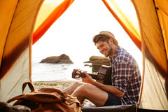 Smiling young man sitting near touristic tent and playing guitar royalty free stock photo