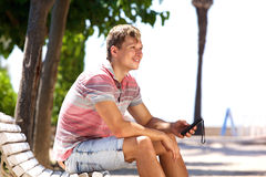 Smiling young man sitting outside with mobile phone Stock Photo