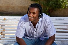 Smiling young man sitting on park bench with headphones Stock Image