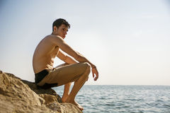 Smiling young man sitting on rock by sea or ocean Royalty Free Stock Photography