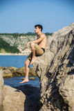 Smiling young man sitting on rock by sea or ocean Royalty Free Stock Photos