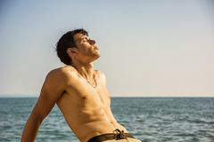 Smiling young man sitting by sea or ocean shore Royalty Free Stock Photos