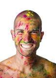 Smiling young man with skin all painted with Holi Royalty Free Stock Photos