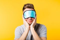Smiling man sleep mask care relaxation rest. Smiling young man sleep mask on. Eye health protection care relaxation rest. Soft comfy supplies products. Lifestyle royalty free stock image