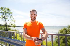 Smiling young man with smart wristwatch at seaside Royalty Free Stock Photography