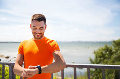 Smiling young man with smart wristwatch at seaside Royalty Free Stock Image