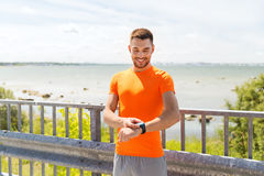 Smiling young man with smart wristwatch at seaside Stock Photography
