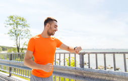 Smiling young man with smart wristwatch at seaside Royalty Free Stock Images
