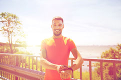 Smiling young man with smart wristwatch at seaside Stock Image