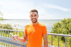 Smiling young man with smartphone and earphones Stock Photo