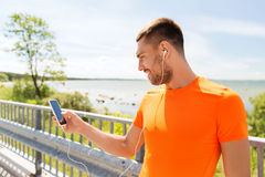 Smiling young man with smartphone and earphones Royalty Free Stock Image