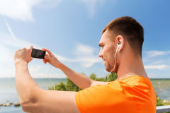 Smiling young man with smartphone and earphones Royalty Free Stock Images