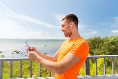 Smiling young man with smartphone and earphones Stock Photos