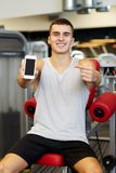 Smiling young man with smartphone in gym Stock Image