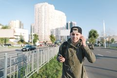 Smiling young man with a smartphone in his hands and headphones in his ears enjoys music while walking around the city. stock photo