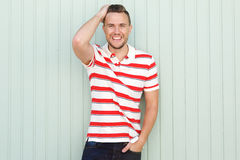 Smiling young man standing against green wall with striped shirt Royalty Free Stock Images