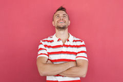 Smiling young man standing against red wall looking up. Portrait of smiling young man standing against red wall looking up Stock Photo