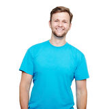 Smiling young man standing. Blue t-shirt design concept. Portrait of a smiling man in blue t-shirt in a studio over a white background royalty free stock photos