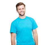 Smiling young man standing. Blue t-shirt design concept. Portrait of a smiling man in blue t-shirt in a studio over a white background stock photography