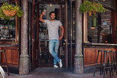 Smiling young man standing at the door of a cafe. Full length portrait of smiling young man standing at the door of a cafe. Relaxed young modern man at a cafe Royalty Free Stock Image