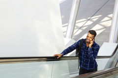 Smiling young man standing on escalator talking on cell phone. Portrait of smiling young man standing on escalator talking on cell phone Royalty Free Stock Photo