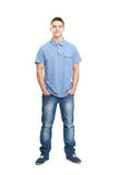 Smiling young man standing with hands in pockets. Full length portrait of smiling young man standing with hands in pockets isolated on white background Royalty Free Stock Photography
