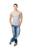 Smiling young man standing with hands in pockets. Full length portrait of smiling young man standing with hands in pockets isolated on white background Stock Photos