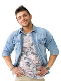 Smiling young man standing with open denim shirt. Handsome young man standing and smiling with open denim shirt, looking at camera, isolated Royalty Free Stock Image