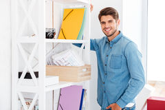 Smiling young man standing at shelf with folders and documents. And looking at camera royalty free stock photos
