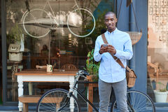 Smiling young man standing in the street reading text messages Stock Photo