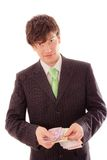 Smiling young man in striped suit and tie holds banknotes Royalty Free Stock Photography