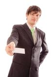 Smiling young man in striped suit and tie shows personal card Royalty Free Stock Photo