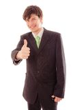 Smiling young man in striped suit and tie shows thumb Royalty Free Stock Photography