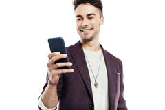 Smiling young man in stylish jacket using smartphone Royalty Free Stock Images