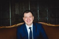 Smiling young man in suite. Young man in blue suit is sitting in wooden chair and smile stock images